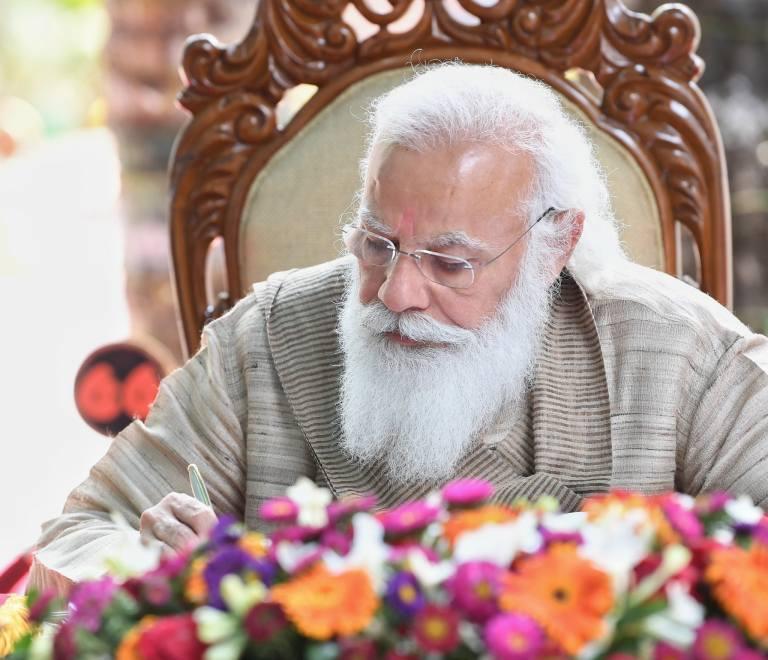 Narendra Modi signing a document